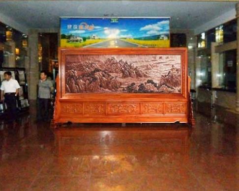 哈尔滨农业发展银行大厅摆放的4.2x2.38米草花梨木祖国颂、迎客松屏风